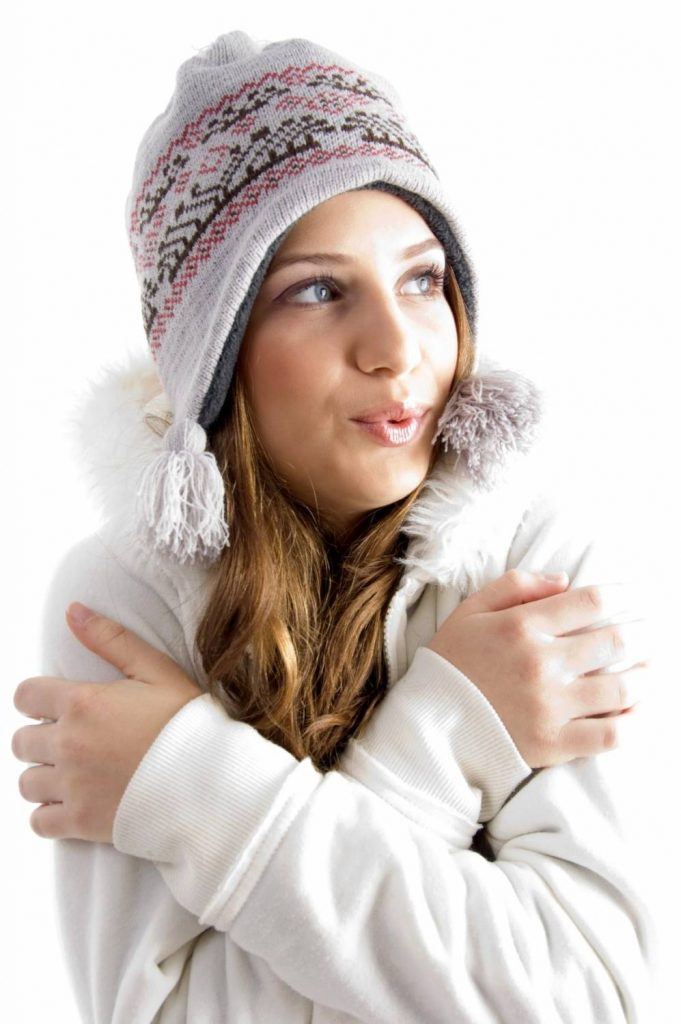 beautiful young female shivering in cold on an isolated background